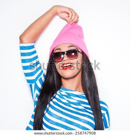 Enjoying her style. Playful young African woman in funky stretching her hat and smiling while standing against white background  - stock photo