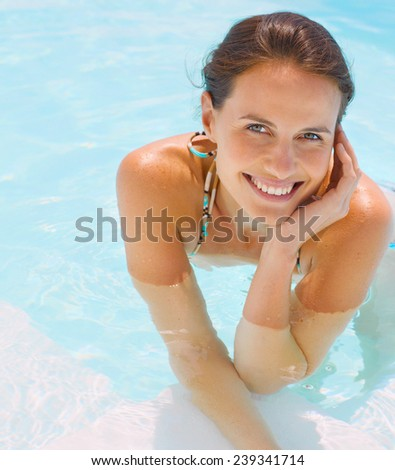 Enjoying her time at the pool - stock photo