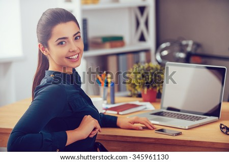 Enjoying her working day. Attractive young woman looking over shoulder and smiling while sitting at her working place in office - stock photo