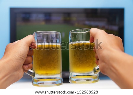 Enjoying his beer in front of the television - stock photo
