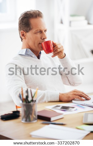 Enjoying his coffee break Confident mature man drinking coffee and looking away while sitting at his working place - stock photo