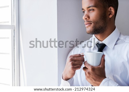 Enjoying his coffee break. Handsome young African man in shirt and tie holding cup with hot drink while looking through the window - stock photo
