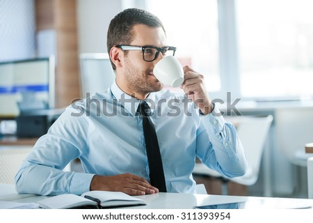Enjoying his coffee break. Handsome young businessman in formalwear drinking coffee while sitting at his working place  - stock photo