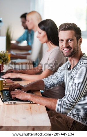Enjoying his creative work. Top view of group of cheerful business people in smart casual wear working at their laptops while handsome man looking at camera and smiling - stock photo