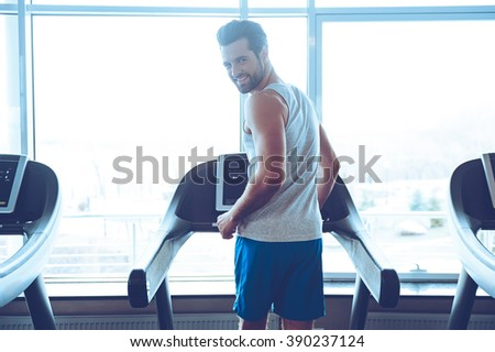Enjoying his exercising. Rear view of young handsome man in sportswear running on treadmill in front of window at gym and looking at camera with smile - stock photo