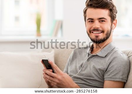 Enjoying his favorite music. Cheerful young man in headphones holding MP3 player and looking at camera while sitting on sofa - stock photo