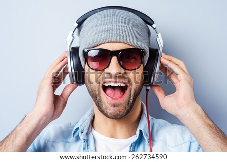 Enjoying his favorite song. Happy young stylish man in headphones expressing positivity and looking at camera while standing against grey background - stock photo