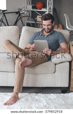 Enjoying his free time at home. Handsome young man using his digital tablet with smile while sitting on the couch at home - stock photo