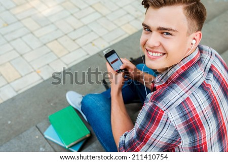 Enjoying his leisure time. Top view of young man listening to MP3 Player and smiling while sitting at the outdoors staircase - stock photo