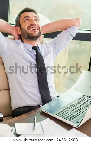 Enjoying his minute break. Handsome mature man in shirt and tie holding hands behind head and smiling while sitting at his working place - stock photo