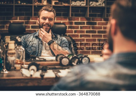 Enjoying his perfect beard. Handsome young bearded man looking at his reflection in the mirror and keeping hand on chin while sitting in chair at barbershop - stock photo