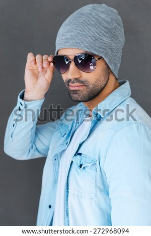 Enjoying his style. Handsome young man in eyewear and headwear posing against grey background - stock photo