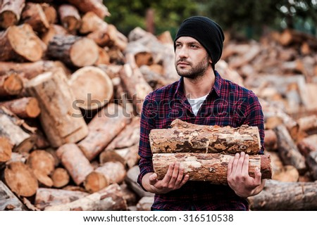 Enjoying his work with wood. Confident young forester holding logs and looking away while standing outdoors - stock photo