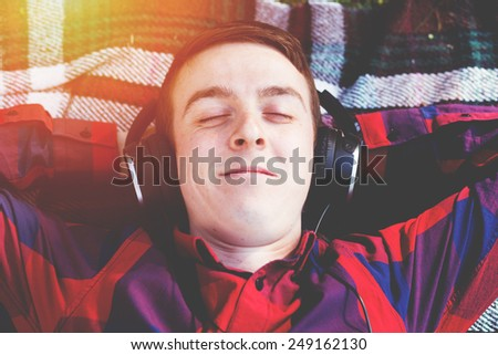 Enjoying in music while laying on the blanket in park - stock photo