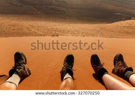 Enjoying landscape and resting after climbing red sand dune in desert. Namibia, Sossusvlei, Naukluft, Africa. - stock photo