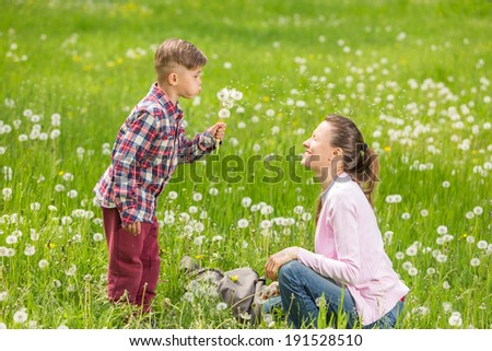 Enjoying life together concept. Happy mother and son having fun outdoors on a sunny summer day - stock photo