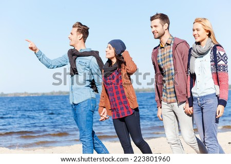 Enjoying life with best friends. Two beautiful young couples walking by the beach together while handsome man pointing away and smiling - stock photo