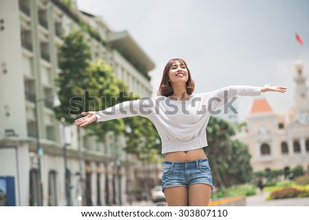 Enjoying life: young woman standing outdoors with her arms outstretched