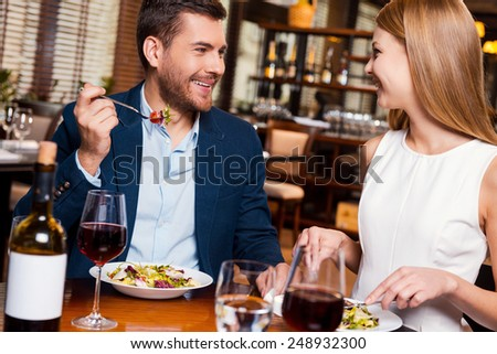 Enjoying meal together. Beautiful young loving couple enjoying dinner at the restaurant  - stock photo
