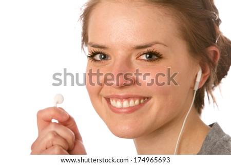 Enjoying Music - This is a photo of a cute young woman ready to listen to some music with her earbuds. Shot on an isolated white background with a shallow depth of field.