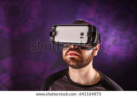 Enjoying new experience. Handsome young man in VR headset