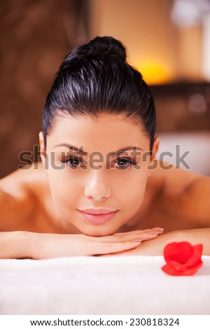 Enjoying relaxation. Front view of beautiful young shirtless woman lying on massage table and looking at camera - stock photo