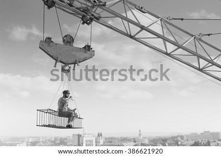 Enjoying rest. Black and white shot of a retro builder drinking milk sitting on a crossbar hanging above the city - stock photo
