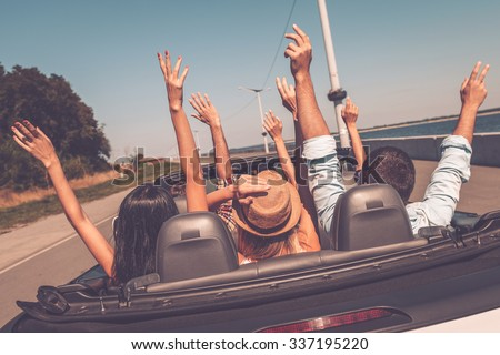 Enjoying road trip. Rear view of young happy people enjoying road trip in their convertible and raising their arms up - stock photo