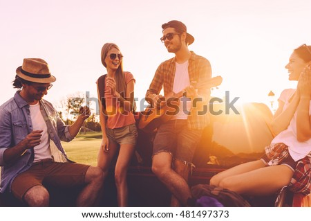 Enjoying road trip with friends. Group of young cheerful people dancing and playing guitar while enjoying their road trip in pick-up truck together
