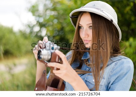 enjoying safari: pretty girl in pith hat taking pictures on camera on green trees summer copy space background, closeup portrait - stock photo