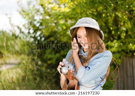 Enjoying safari: Young beautiful woman in pith hat taking pictures on retro film camera on green trees summer copy space background - stock photo