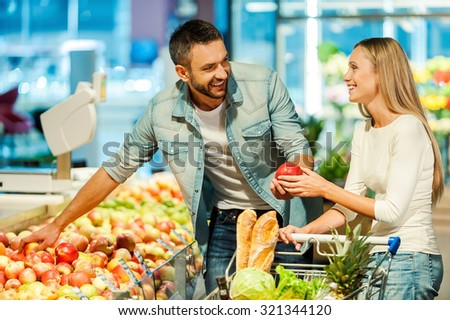 Enjoying shopping together. Beautiful young smiling couple choosing apples in supermarket together  - stock photo
