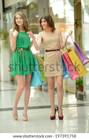 Enjoying shopping. Two beautiful young women shopping together and talking