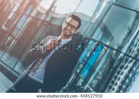 Enjoying successful day. Smiling young businessman adjusting his necktie and looking at camera while standing outdoors with office building in the background