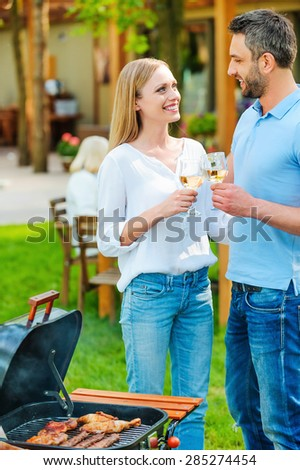 Enjoying summer barbeque. Happy young couple barbecuing meat on the grill and drinking wine while other members of family sitting at the dining table in the background  - stock photo