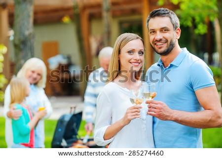 Enjoying summer barbeque with family. Happy young couple bonding to each other and holding wine glasses while other members of family barbecuing food in the background  - stock photo