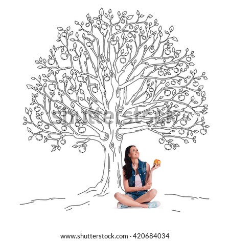 Enjoying summer. Beautiful young cheerful woman holding apple and looking up with smile while sitting in lotus position under sketch of apple tree  - stock photo