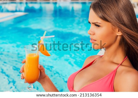 Enjoying summer by the pool. Side view of beautiful young woman in bikini holding cocktail while sitting by the pool - stock photo