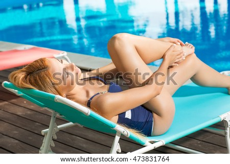 Enjoying summer days. Horizontal shot of a stunning red haired female lying on a lounge chair by the swimming pool