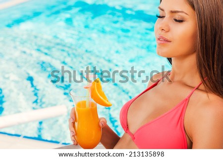 Enjoying summer time. Side view of beautiful young woman in bikini holding cocktail and keeping eyes closed while sitting by the poolEnjoying summer time.  - stock photo