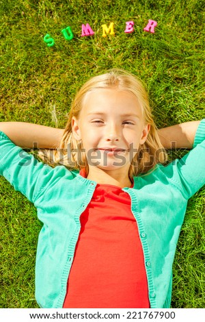 Enjoying summer time. Top view of cute little girl holding hands behind head and smiling while lying on the green grass with plastic colorful letters laying upon her head - stock photo