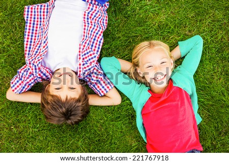 Enjoying summer time. Top view of two cute little children holding hands behind head and smiling while lying on the green grass together - stock photo