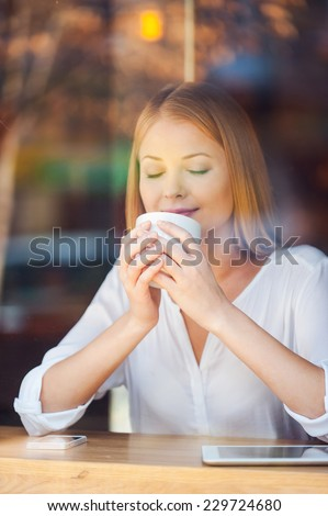 Enjoying the best coffee in town. Through a glass shot of beautiful young woman keeping eyes closed and smiling while enjoying coffee in cafe  - stock photo
