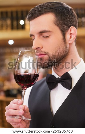 Enjoying the best wine. Confident young man in waistcoat and bow tie keeping eyes closed while holding wine glass with red wine and smelling it