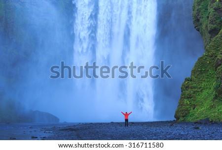 Enjoying the famous Skogarfoss waterfall in southern Iceland. - stock photo