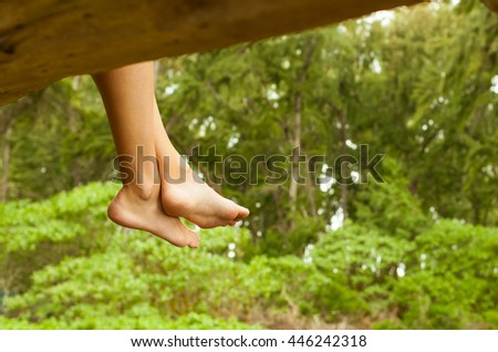 Enjoying the great outdoors. Pair of feet relaxing in a beautiful outdoor green setting.  - stock photo