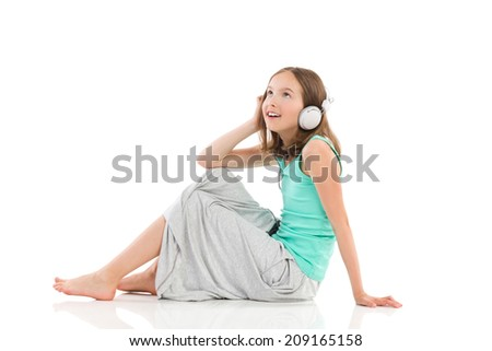 Enjoying the music. Young girl with headphones is sitting on the floor, listening to the music and looking up. Full length studio shot isolated on white. - stock photo