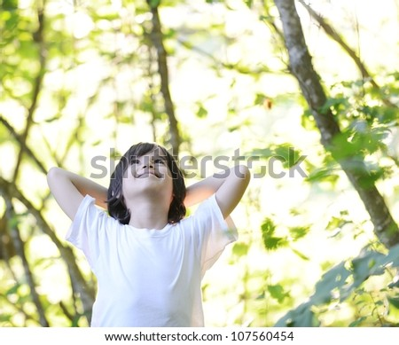 Enjoying the nature. Cute little boy with arms raised enjoying t - stock photo
