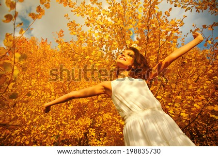 Enjoying the nature. Young woman arms raised enjoying the fresh air in autumn forest. - stock photo