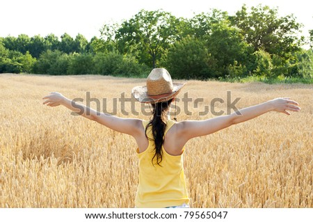 Enjoying the nature - Young woman arms spread enjoying the fresh air in wheat field - stock photo